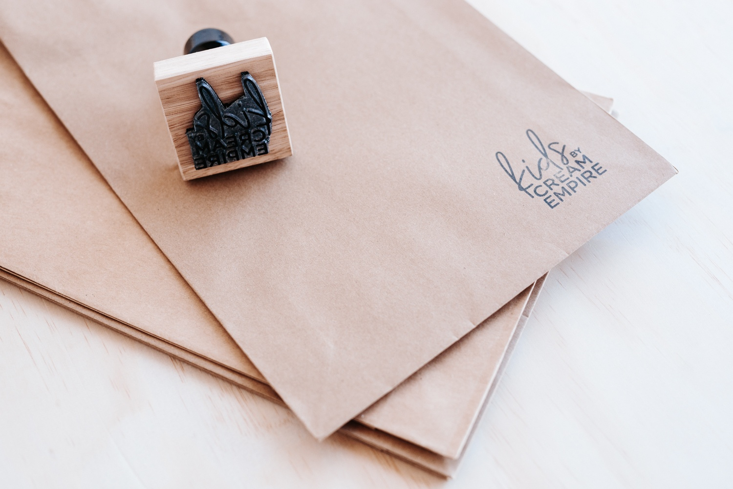Brown paper bag branded with a rubber stamp: Kids by Cream Empire