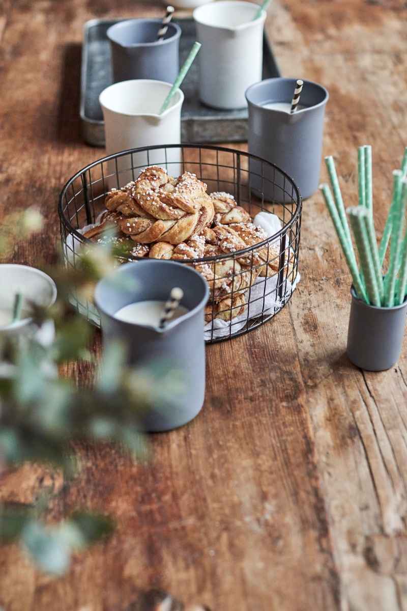 A wire dish of pastries on a rustic wooden table surrounded by grey beakers of milk with paper straws