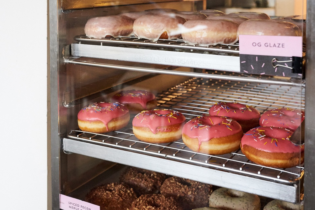 Rows of colourful glazed donuts on racks as viewed through an oven window