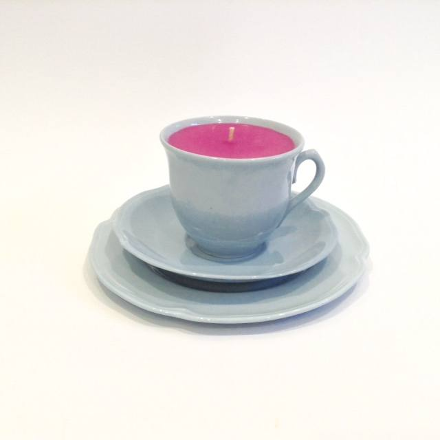 A teacup candle set against a clean white backdrop