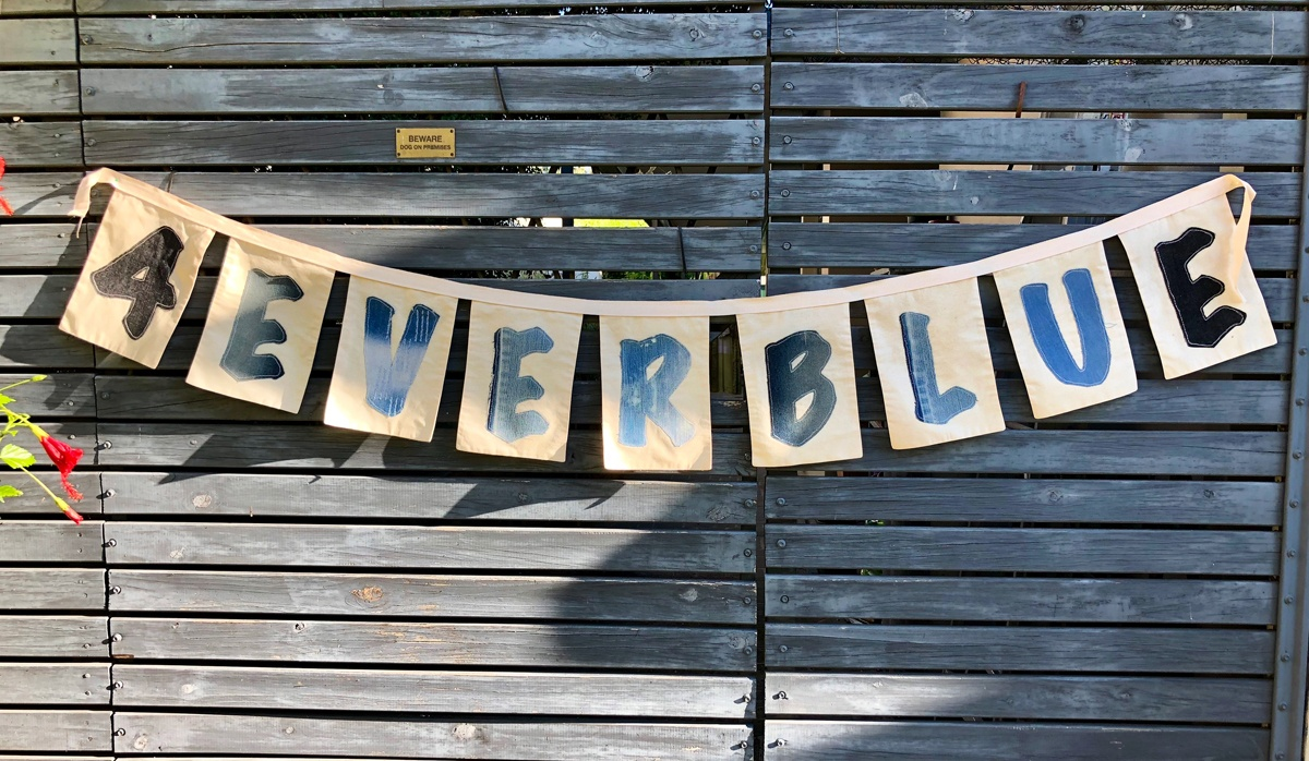 4Ever Blue Creations handmade sign against a weathered timber fence