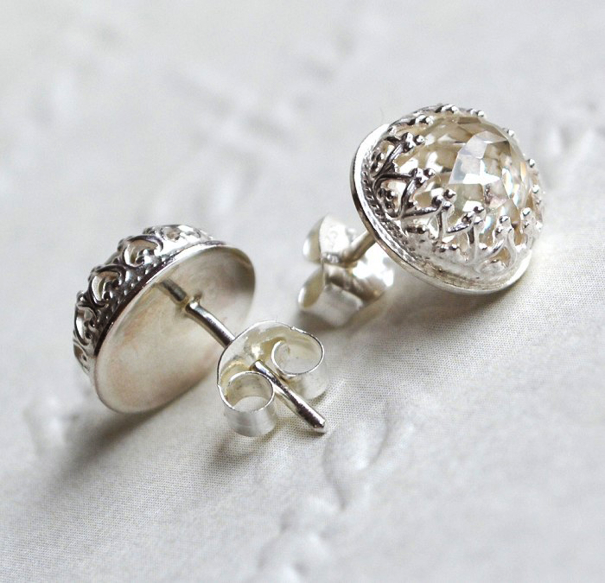 White topaz studs with crown detail in eco-friendly sterling silver.