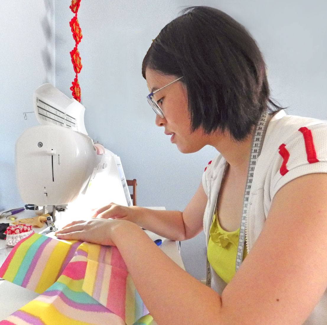 Christina, designer and maker of CLEAN the Label, working at her sewing machine on a brightly striped shirt
