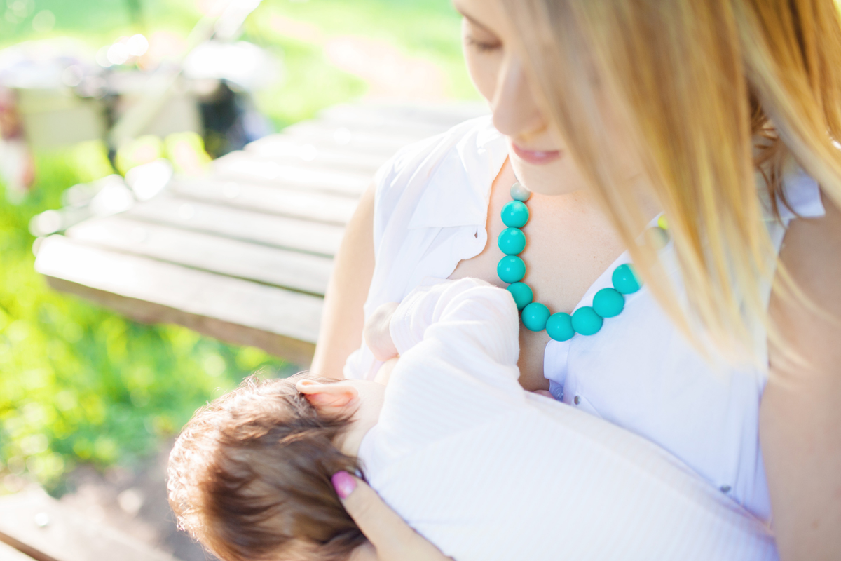 A pretty aqua teething necklace in use""