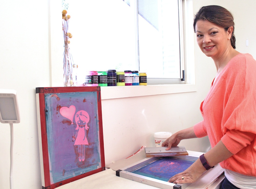 Ari screen-printing her own textiles in her home workspace