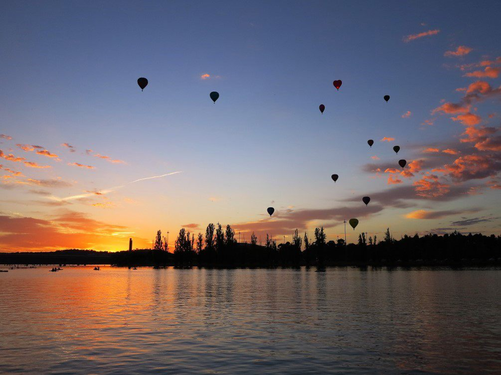 Silhoettes of hot air balloons against a Canberra sunset