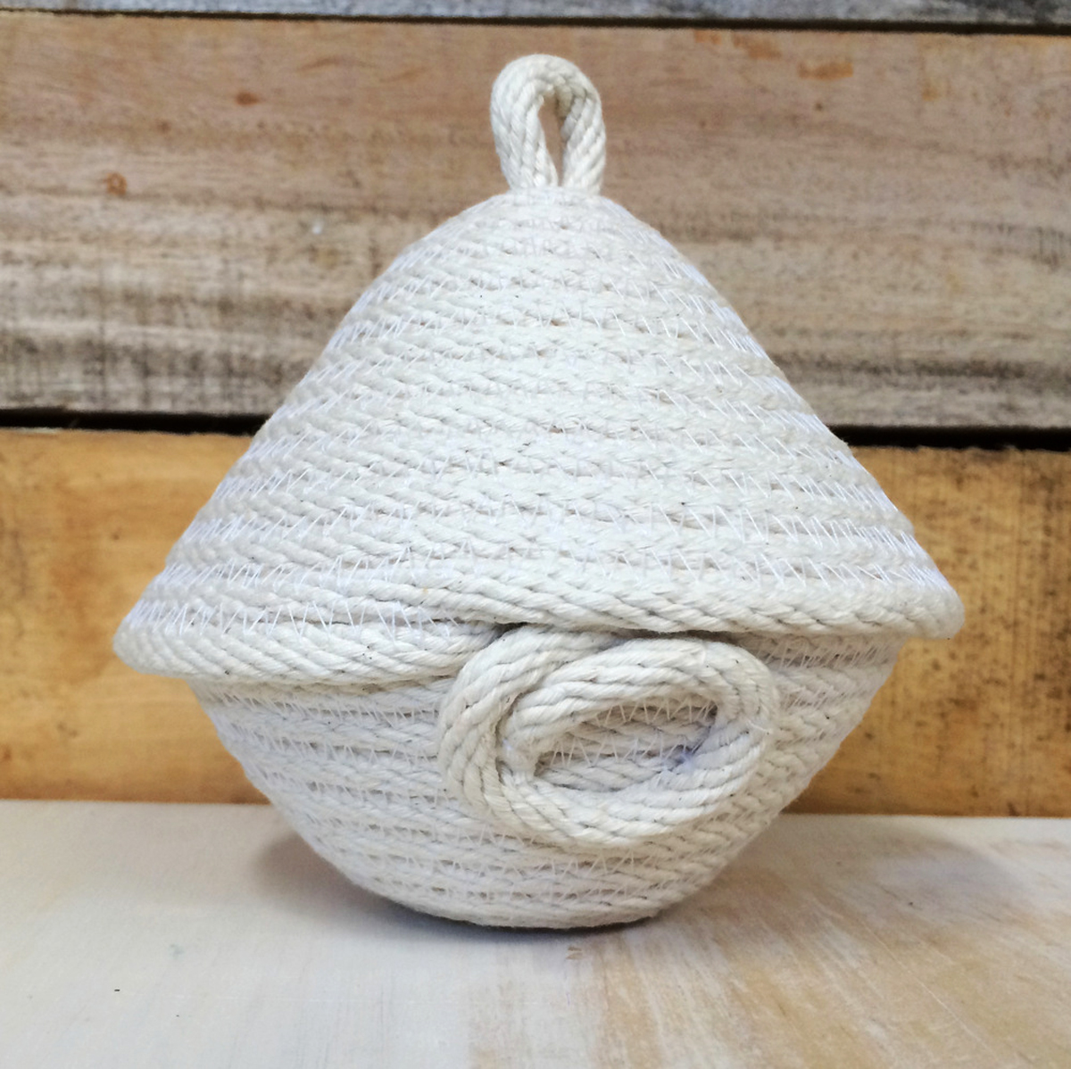 A natural coiled rope pot with lid