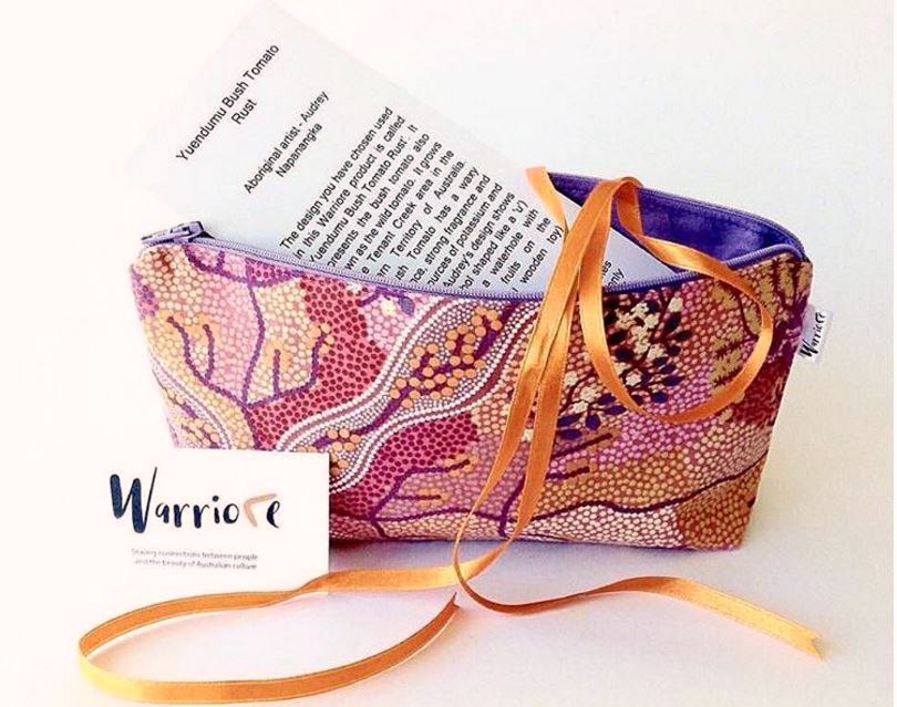 A Warriore bag in Audrey Napanangka's Yuendumu Bush Tomato Rust fabric with explaination of the artwork.
