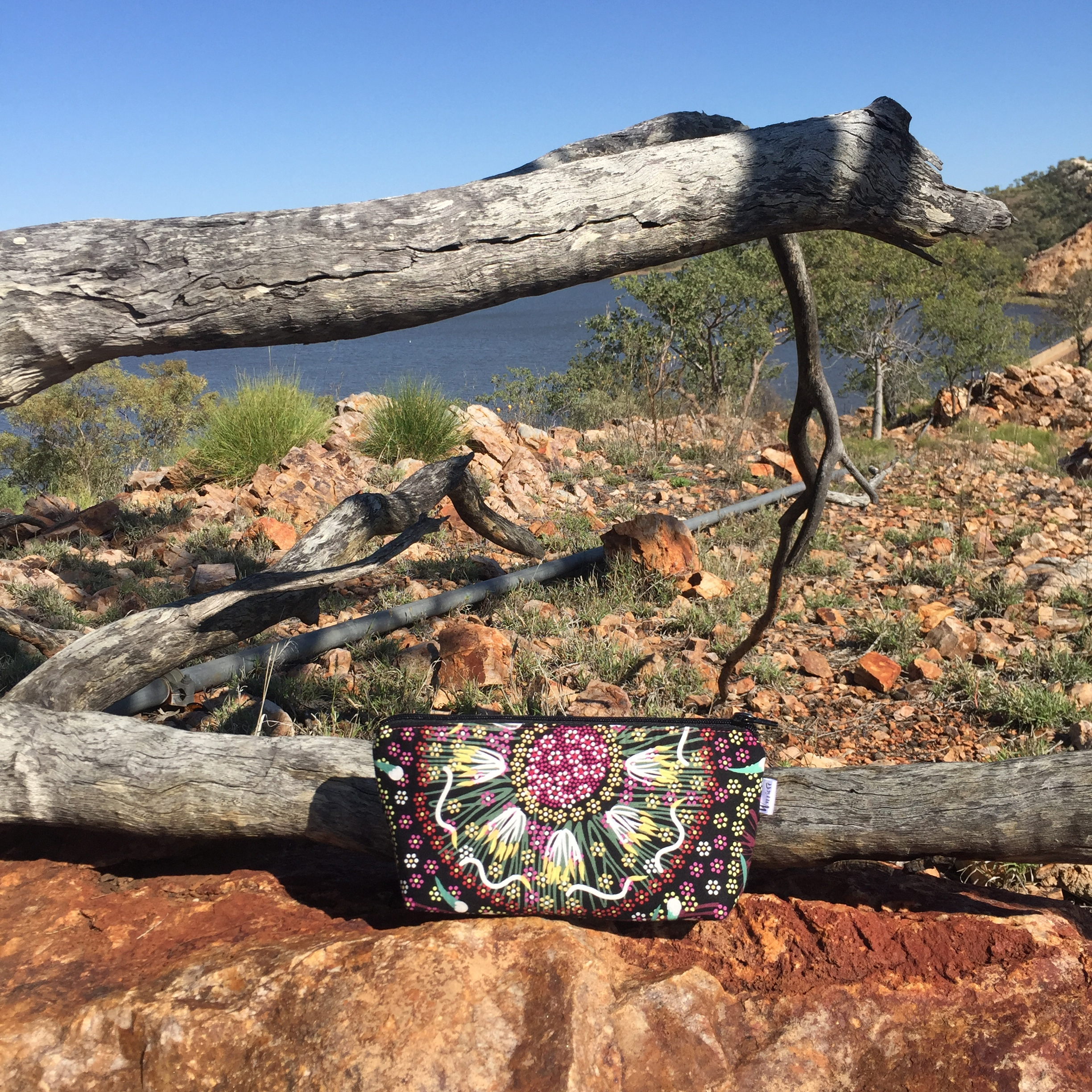 A Warriore bag in Aboriginal Plum & Bush Banana fabric set against a rocky outcrop in Mt Isa: