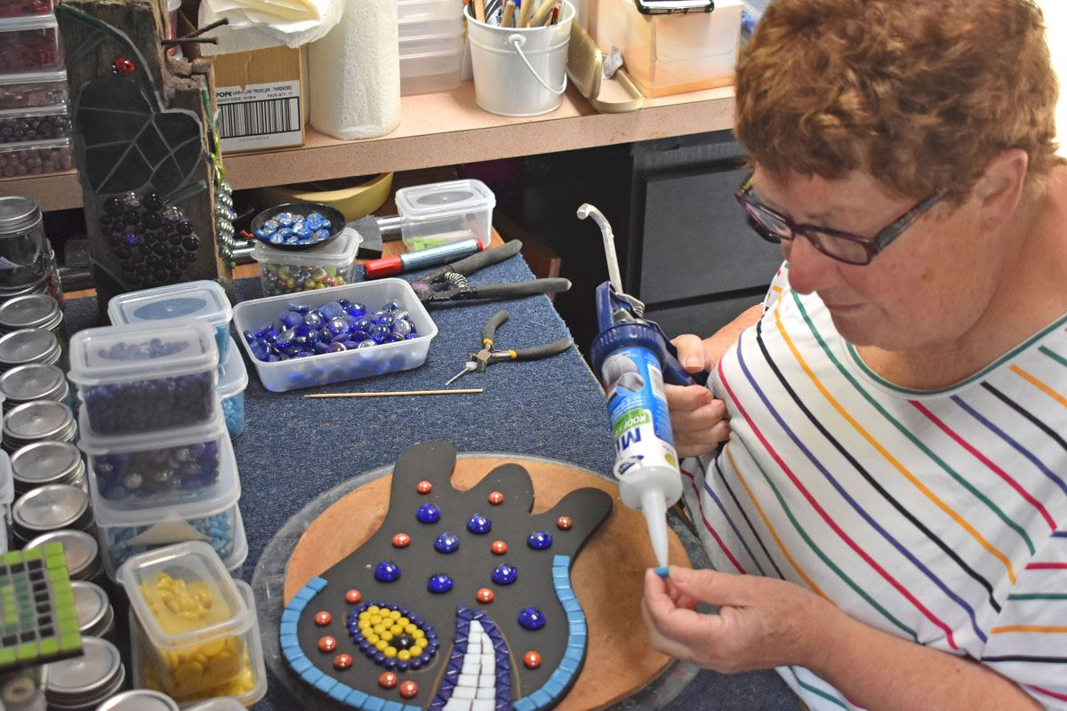 Diane at work on a whimsical mosaic creature, gluing glass tesserae in place.