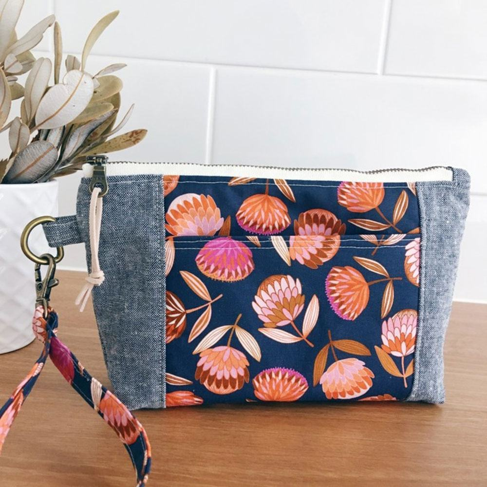 A handcrafted Banksia and Bloom wristlet purse in pink and orange Joselyn Proust protea print on Navy with grey linen panels.
