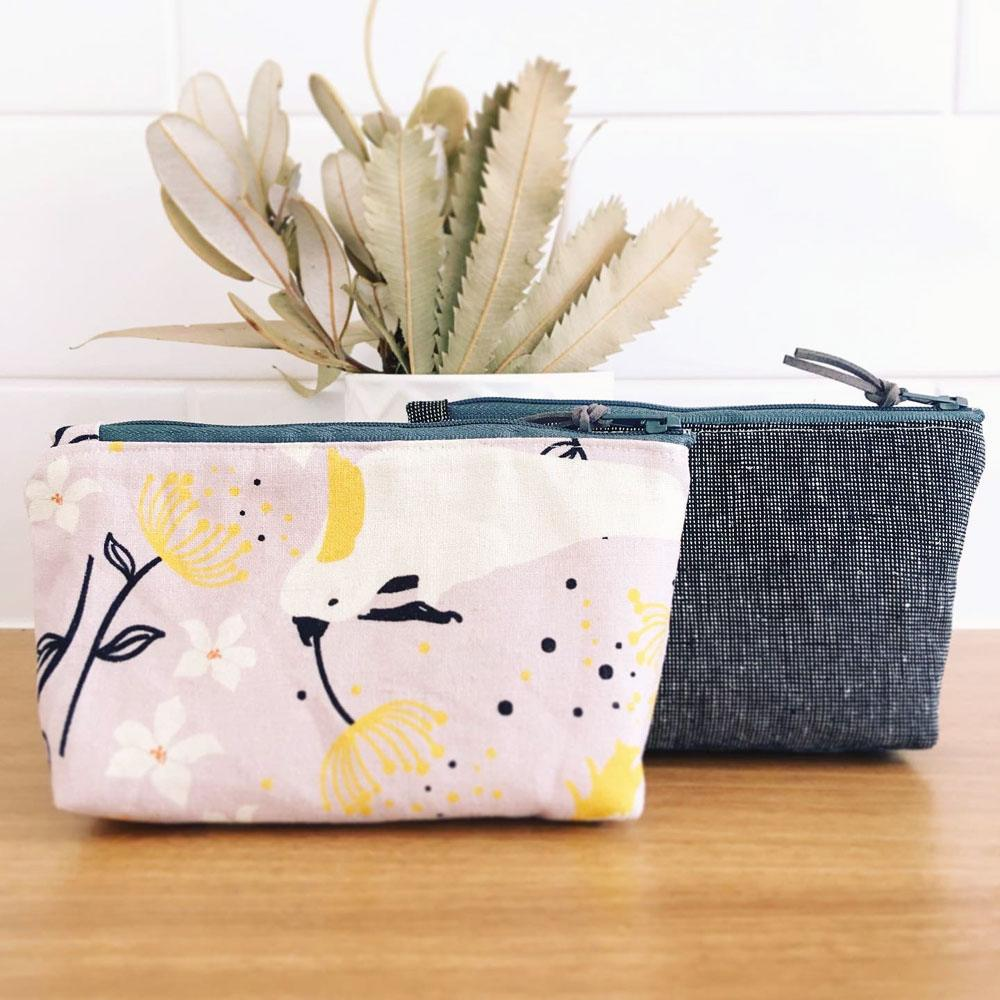 A pair of Banksia and Bloom zipper pouches; one in a grey linen and the other in a cockatoo and gum blossom print