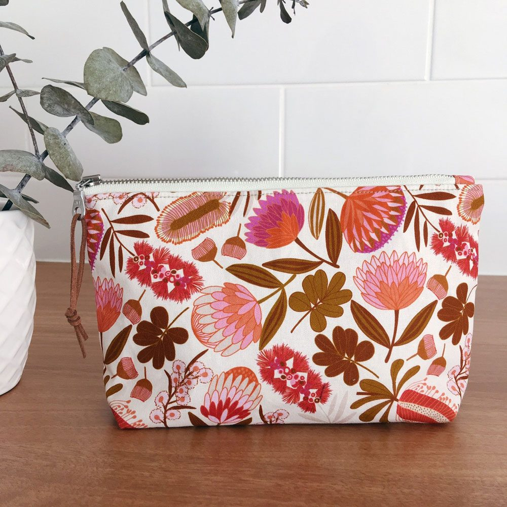 One of Caroline's handmade pouches in a striking orange and pink Joselyn Proust native bouquet print'