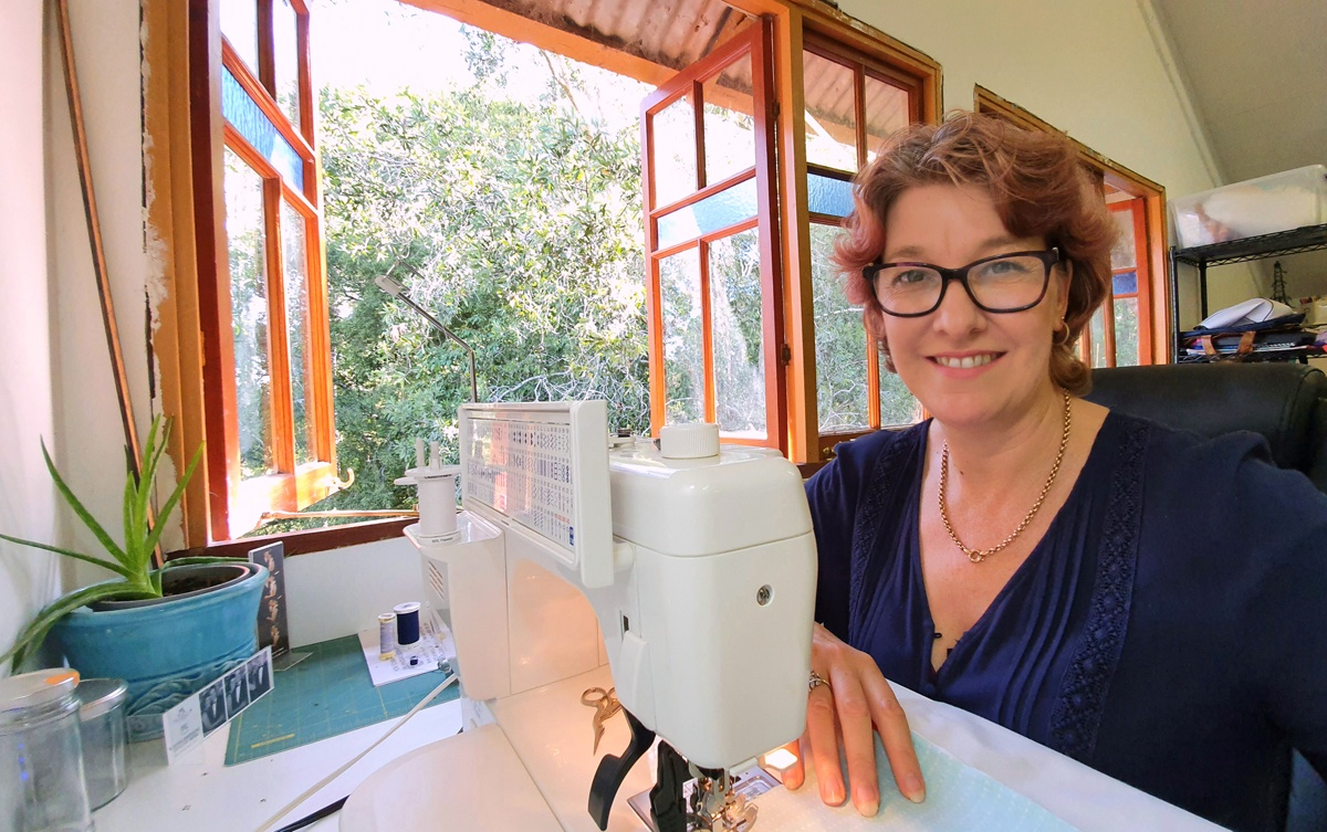 Marceliena at her sewing machine in her light-filled home studio overlooking the treetops