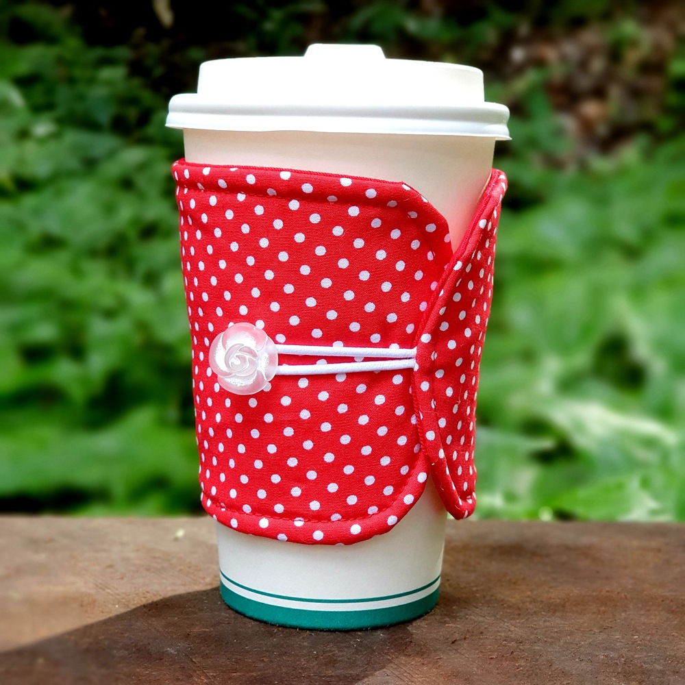 A bright red fabric cup cosy wth white polka dots and carved rose button detail by Birdy & The Boys