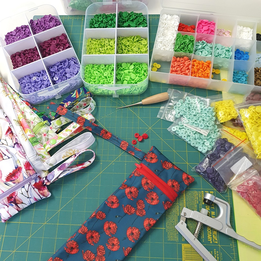 Marceliena's work bench covered in colourful buttons and a range of umbrella covers in progress