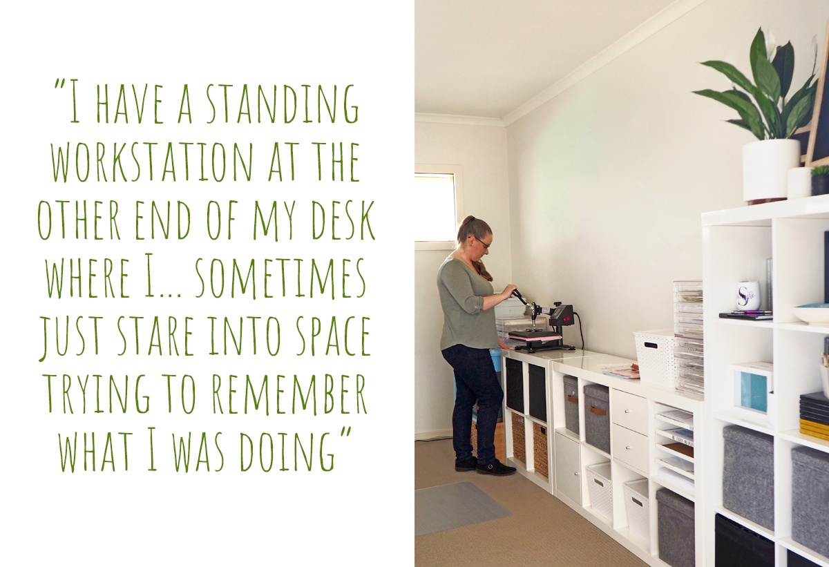Emma at work in her home craft space, applying designs to end products; 'I have a standing workstation at the other end of my desk where I… sometimes just stare into space trying to remember what I was doing'
