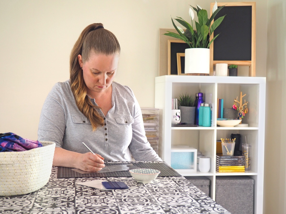 Emma at work cutting a personalised design in her Victorian home craftspace