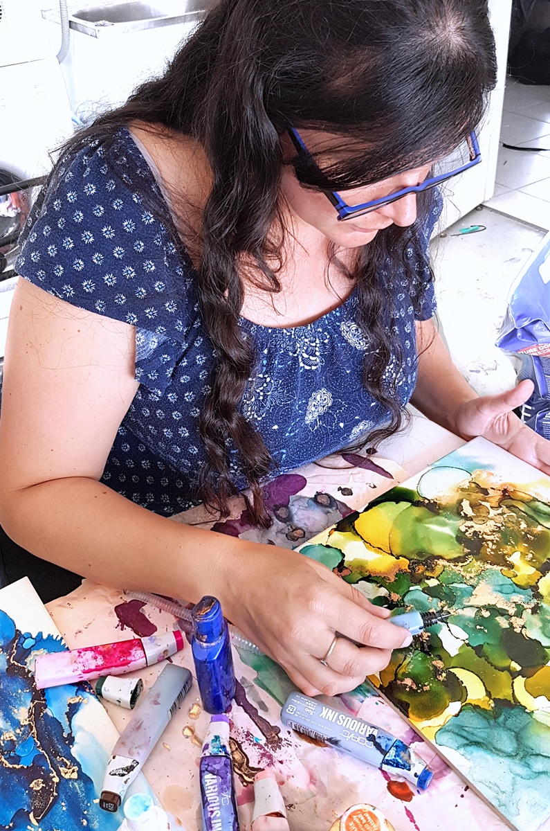 Belinda at work on an alcohol ink painting in her garage painting studio