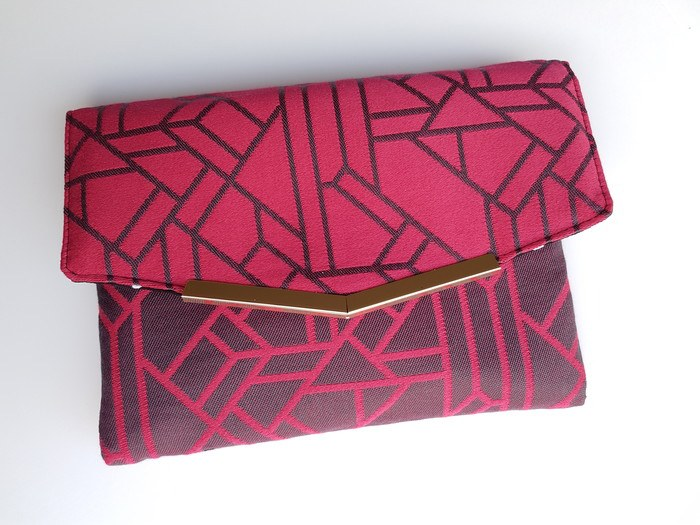 The Vivi clutch in geometric red, upcycled from scrap fabric of a Ankalia Shoalhaven Vermillion woven wrap and finished with gold tone hardware