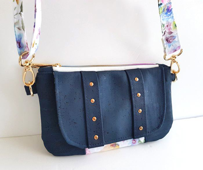 Navy blue cork leather structured compact clutch purse with contrasting floral fabric accent and strap and gold tone hardware