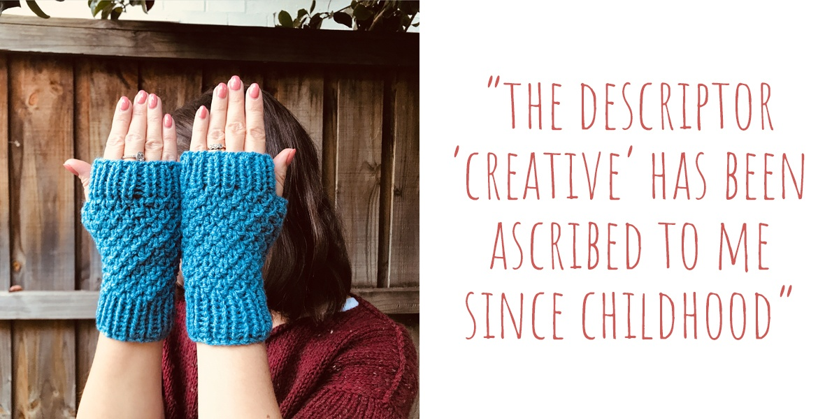 Carolyn reluctantly modelling a pair of her crochet fingerless gloves: 'The descriptor 'creative' has been ascribed to me since childhood'
