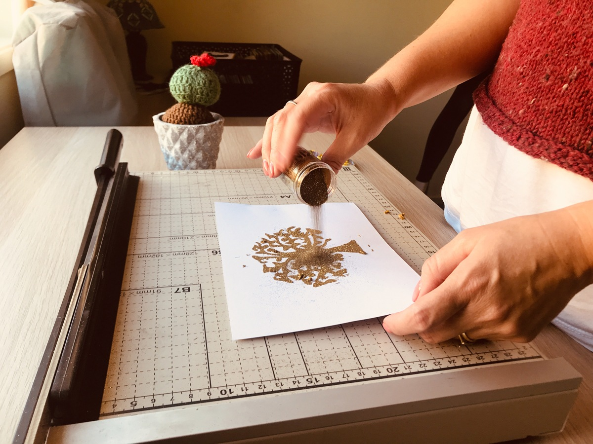 Card-making process: adding sparkling gold embossing powder