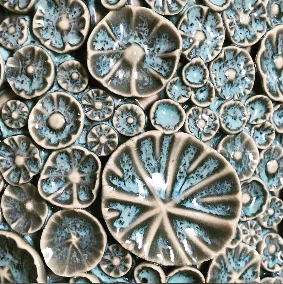 Close-up detail of aqua blue glazed ceramic barnacles and florets from one of Nicole's earthenware pieces