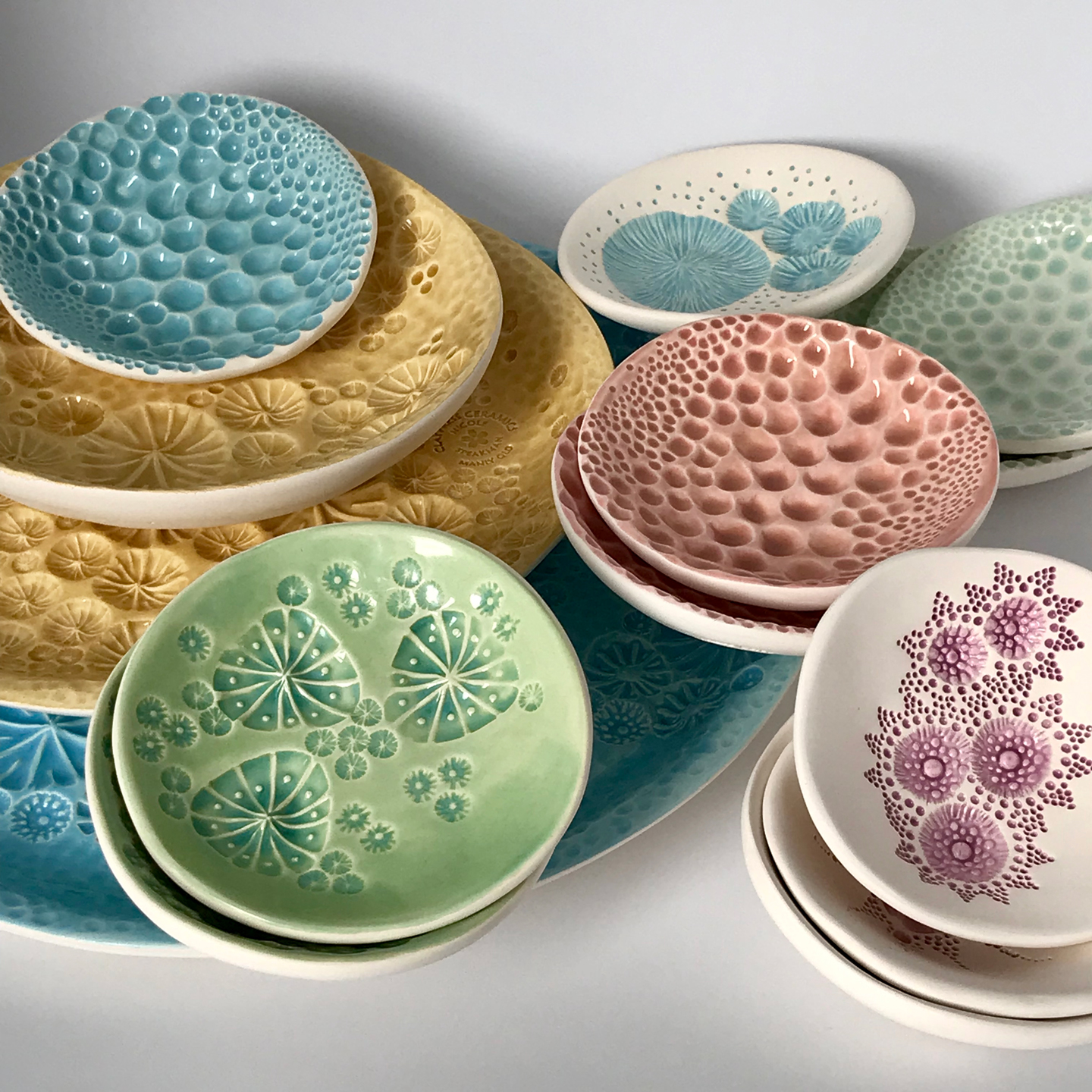 A collection of embossed ceramic plates in colourful glazes by ClayPress Ceramics