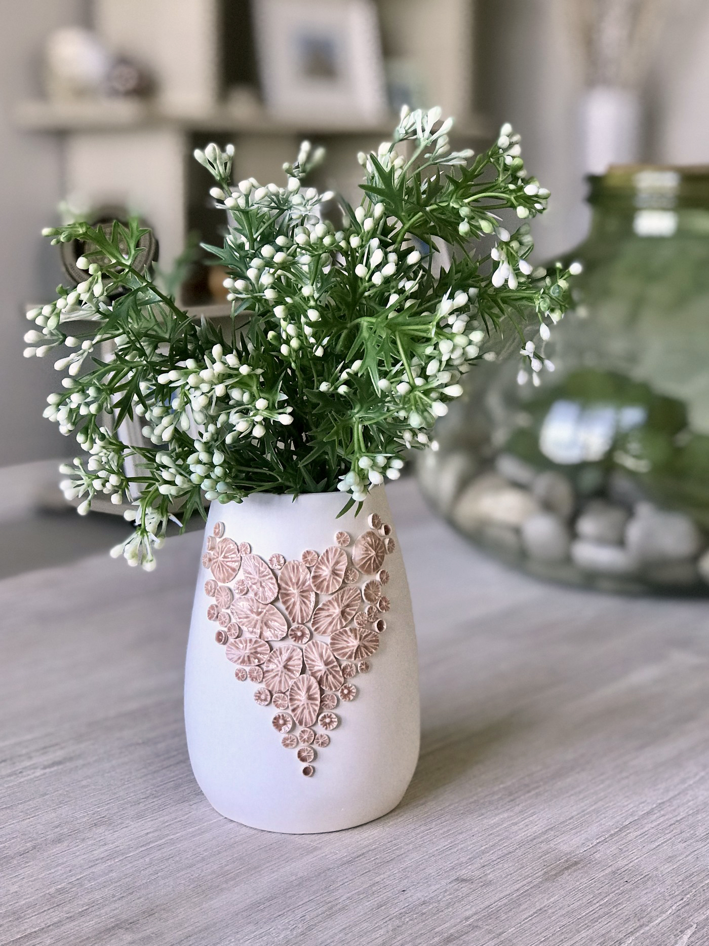 Smooth, matt white earthenware vase with a blush pink glazed heart shaped arrangement of coral polup-like embelishments