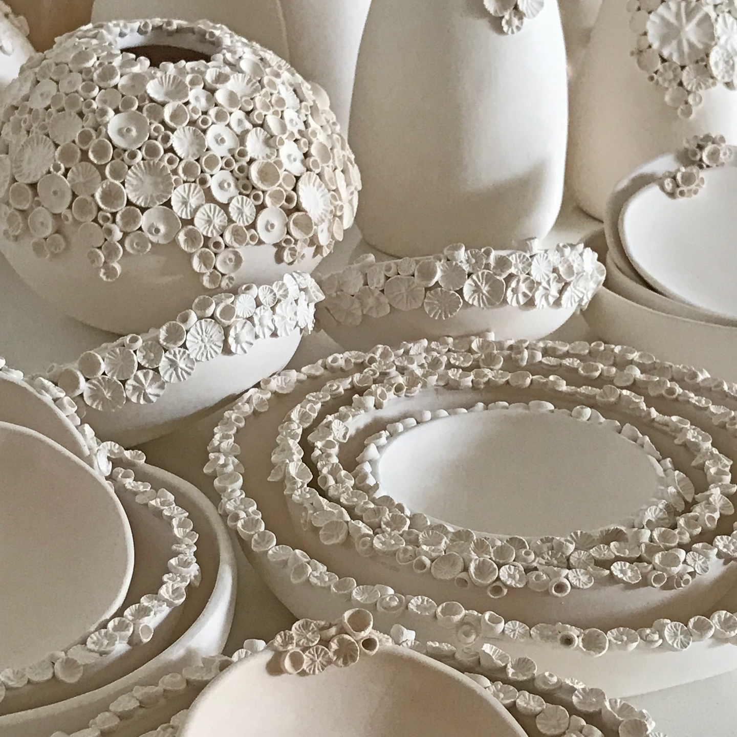 An array of bisque (unglazed, fired) ceramic vases and bowls adorned with coral-like 3d details by ClayPress Ceramics