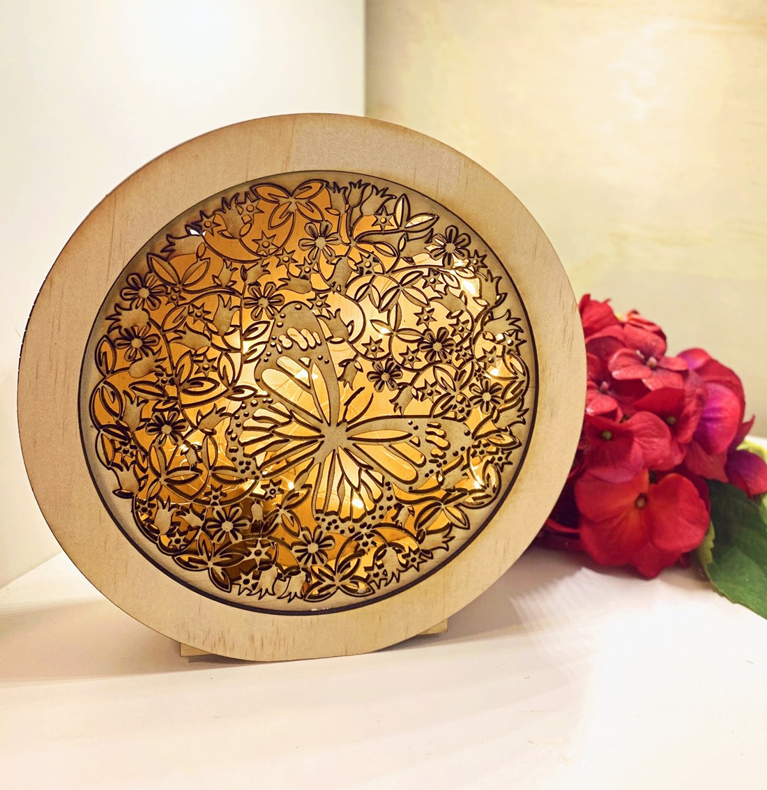An intricately laser-cut round timber lightbox in a butterfly and floral design, created by Crafty Weasel