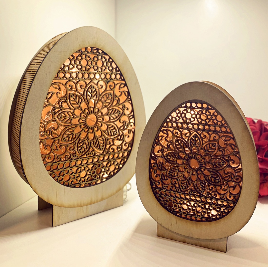 Egg-shaped timber light boxes laser cut with detailed floral designs