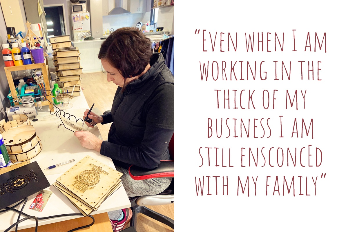 Esther at work cutting designs into timber panels in her living room workshop; 'Even when I am working in the thick of my business I am still ensconced with my family