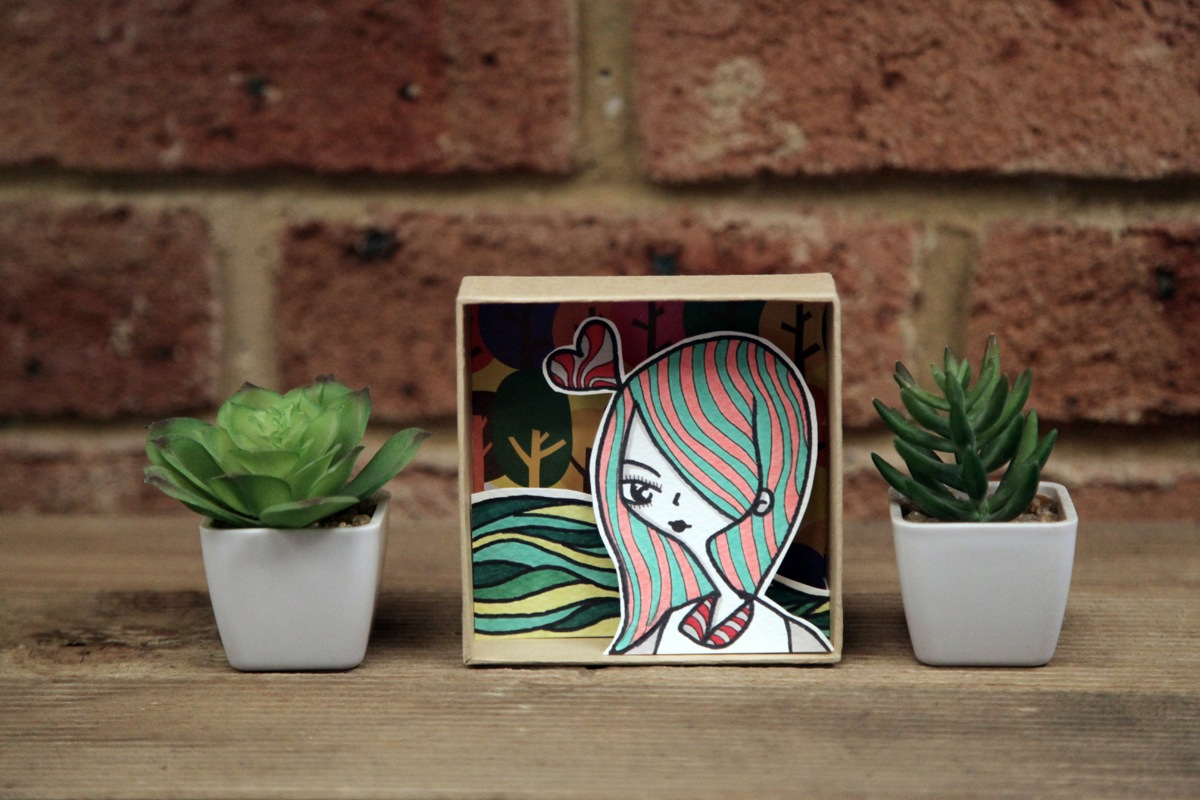 A handmade cardboard shadow box with layered illustrations by dentanARTS