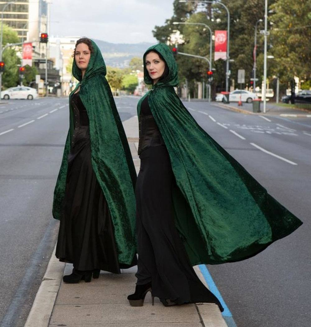 Two women crossing a busy urban road, dressed in all black except their striking emerald green hooded velour cloaks by Dragon's Blood Creations