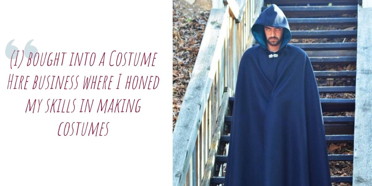 A man in a full-length dark hooded wool cloak descends the stairs: '(I) bought into a Costume Hire business where I honed my skills in making costumes'