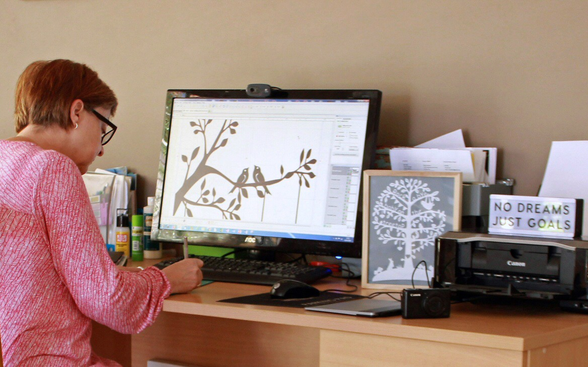 Lesley at work on a papercut design in her home work-space