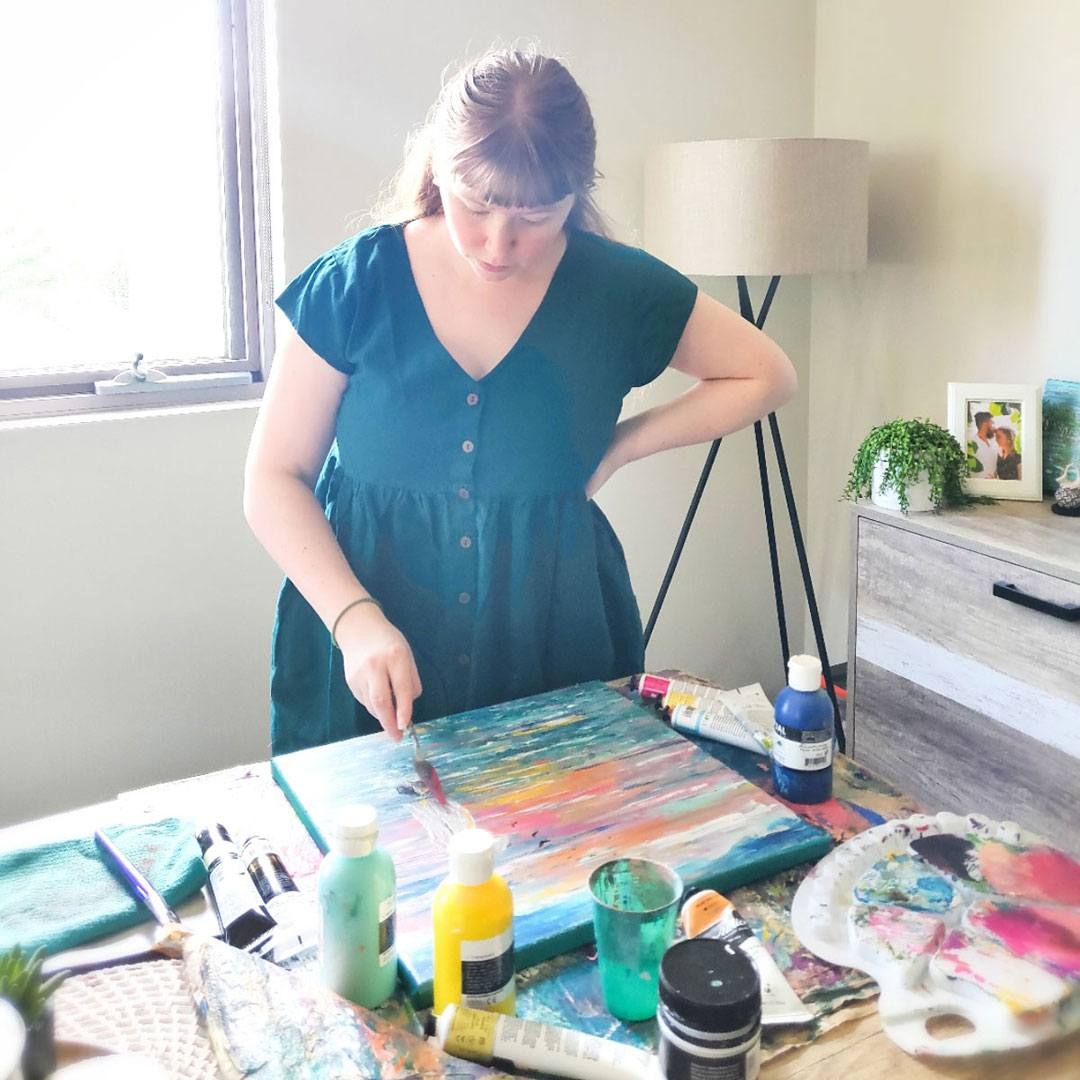 Breanna from Ensorcell Creations at work on an acrylic on canvas painting in her living room
