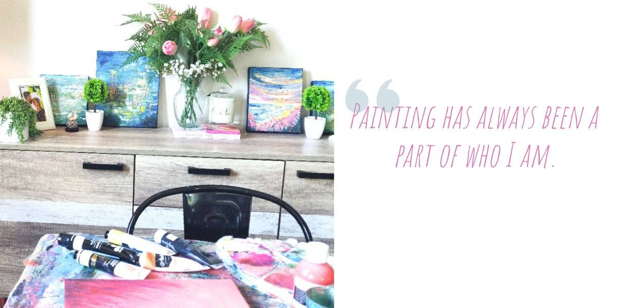 Breanna's living room table covered in brightly coloured paints, canvas and palettes with a collection of her works on the buffet behind: 'Painting has always been a part of who I am.'
