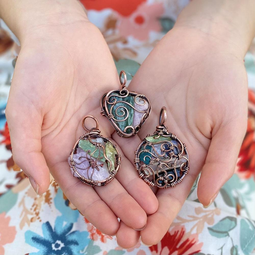 Kel holding a collection of Esse Lux copper-wire-wrapped crystal pendants in her palms