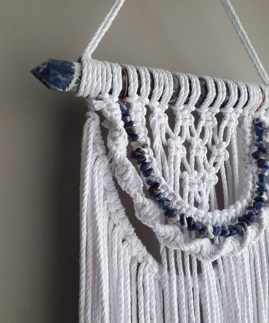 An Esse Lux macrame wall-hanging with integrated string of blue stones