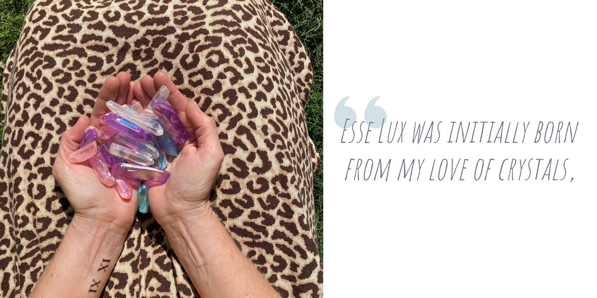Kel kneeling on the grass holding a collection of pretty pastel crystals in her lap; 'Esse Lux was initially born from my love of crystals'