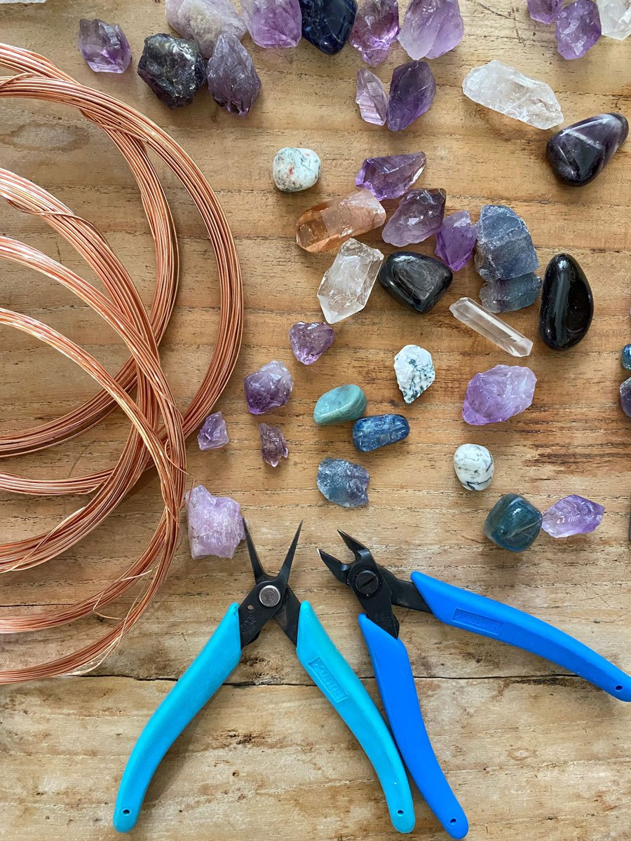 Tools of the trade: A collection of raw crystals, copper wire and jewellery plyers on a timber background