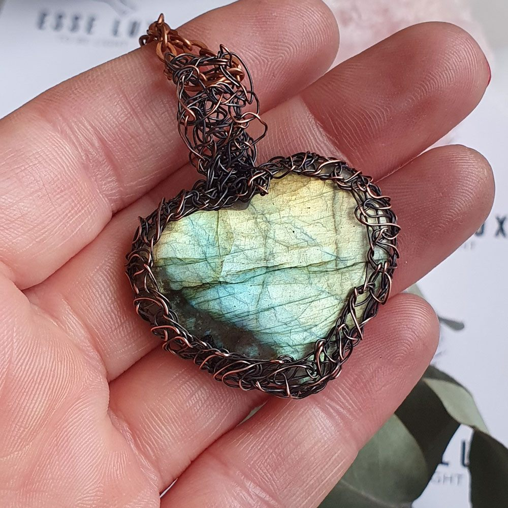 An intricately wire-wrapped pendant with heart-shaped labradorite stone
