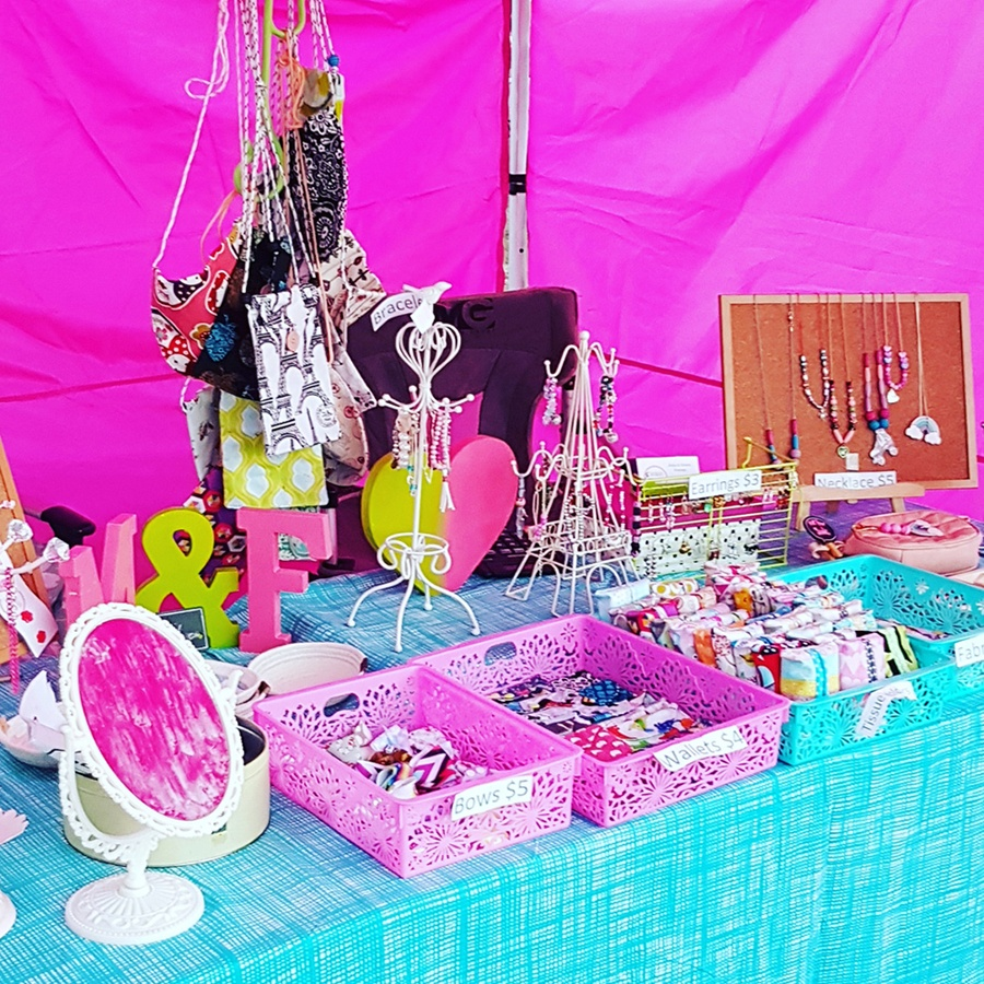 Closeup of a brightly coloured market display of jewellery , purses and other accessories by Freckles & Moo