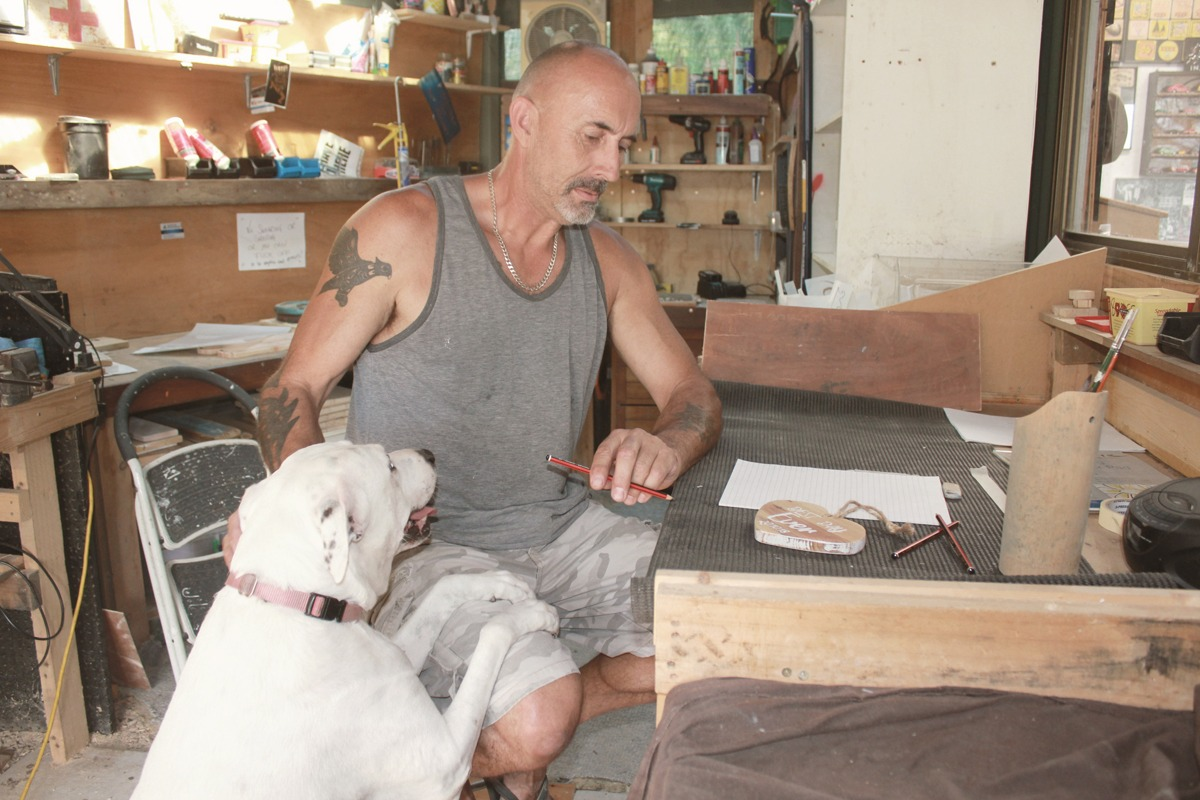 Clint and dog, Bonnie, coming up with new sign designs in the workshop
