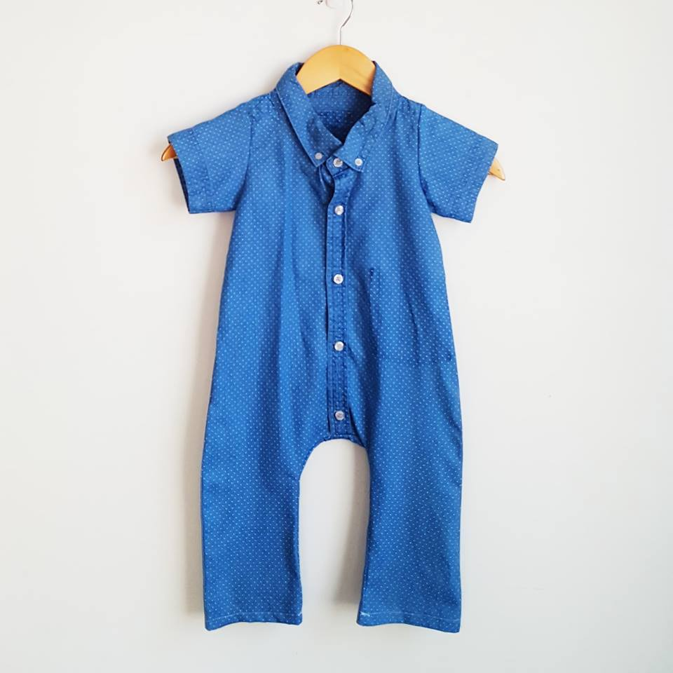 A blue short-sleeved collared romper with a very fine polkadot pattern, hanging against a plain white wall.
