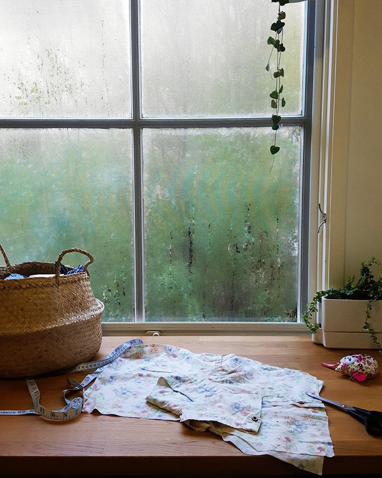 A salvaged shirt in the process of being recreated at Hywell's workstation, looking out onto her garden through a fog-covered window""