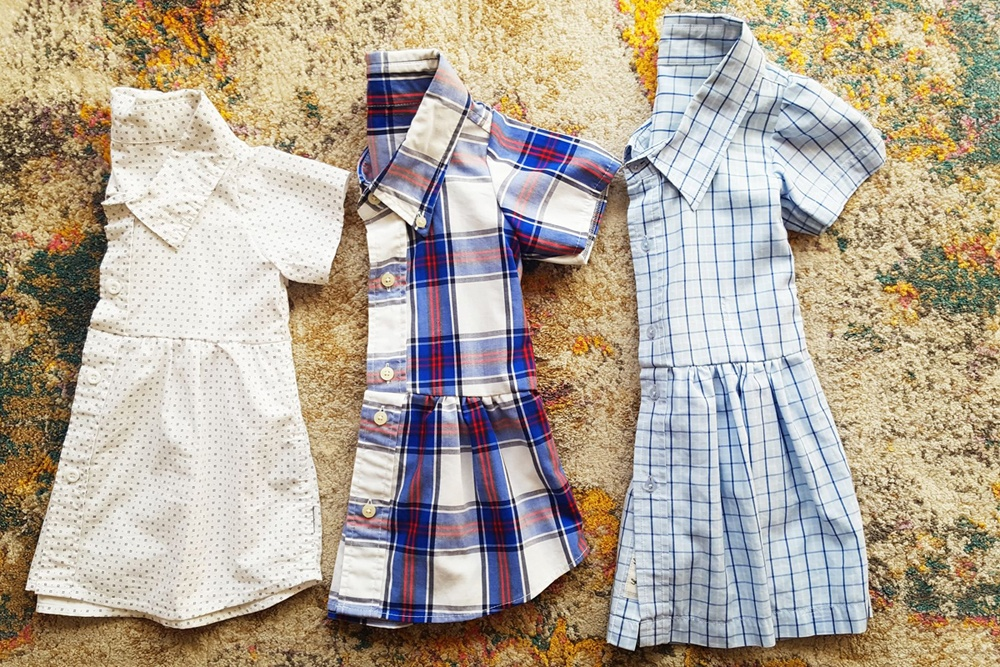 Three collared shirts repurposed into children's dresses, againsta a backdrop of vintage carpet""